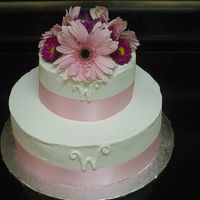 "Simply Pink Buttercream with real ribbon around the edge. Flowers on top! Piped a ""W"""