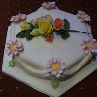 80Th Rose Hexagonal Sponge covered with fondant dahalias at each point with luster sprayed swags in between and a boquet of roses on top was made for...