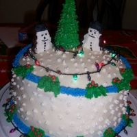 My First Christmas Cake.  yellow cake mix, all butter cream icing,Christmas tree made out of ice cream cone,snowmen made out of homemade cookies, lights are from...