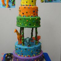 Jungle Birthday Cake  Colorful tiered birthday cake with Mexican Paste lions, giraffe and elephant. Cake was created to compliment a fabric tablecloth matching...
