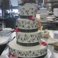 Pink/grey Wedding All buttercream with charcoal grey ribbon and scroll work. Fresh flowers/petals.
