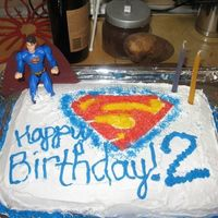Superman sheet cake with sugar sprinkles stenciled on - and an action figure stuck in it!