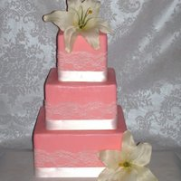 Classic Romance. Cake is wrapped in a pretty pink fondant, then w/white lace, then a white satin ribbon. Flowers are white silk lilies. Yes, I realize a lot...
