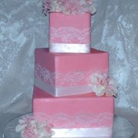 Soft Romance. Cake is wrapped in a pretty pink fondant, then w/white lace, then a white satin ribbon. Flowers are mini bouquets of white silk hydrangea &...