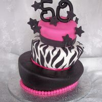 "Topsy Turvy 50Th Topsy Turvy 50th birthday cake. Carved 6"", 8"", 10"" tiers. SI fondant."