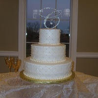 Quilted Pearls & Rhinestones Wedding Cake Ivory quilted pattern with edible pearls and a rhinestone topper.