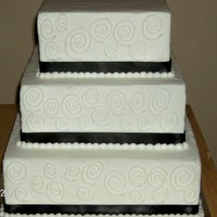 Anna   3 tier buttercream square step stacked black ribbon and circular scrolls