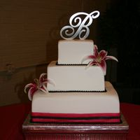 Simple Square Fondant Cake 3 square cakes wrapped in fondant, with fondant pearls and a fondant ribbon on bottom tier. Flowers are real. Colors are black and...