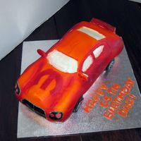 Dodge Charger With the Mopar logo for a man who works for them. Modeling chocolate, fondant, airbrushed.