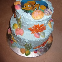 Nemo Finding Nemo theme. Buttercream icing, edible image on top, hand painted white chocolate shells and royal icing corals.