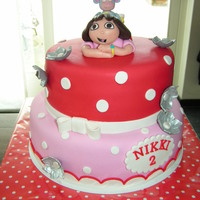 Dora The Explorer Dora and boots on top of a red and pink polkadot cake!