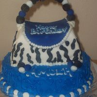 Blue/black Purse bottom (blue) cake is chocolate cake with buttercream icing, the purse is white cake with buttercream incing covered with fondant!