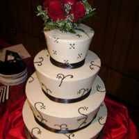 Rose All buttercream iced with buttercream designs. Beautiful fresh red roses top the tapered tiers with black ribbon on the bottoms of each...