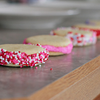 Valentine Cookies Bite size Sugar cookies cut out with the rim of a shot glass with BC sandwiched in between two cookies then rolled in sprinkles