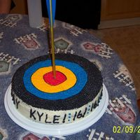 "Bullseye  2 layer 12"" rounds with BC icing and a real arrow in the middle. It was a new arrow with plastic wrap covering the metal touching the..."