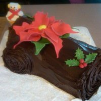 Yule Log   chocolate cake with almond buttercream filling. chocolate fudge frosting. gumpaste pointsettia and holly leaves/berrries.