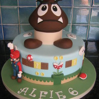 "Super Mario Cake 11"" chocolate sponge cake with vanilla b/c and caramel filling, covered in fondant with gumpaste figure.Thanks for looking."