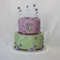 "Purple Green & Brown W/ Flowers 6"" 8"" Rounds iced in buttercream with fondant flowers and wire curly-q's on top."