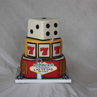 "Married In Fabulous Las Vegas 5"" square top tier, 8"" round middle tier, 9"" square bottom tier with corners cut. Iced in fondant with sugar decorations."