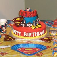 Superman White cake filled w/ dulce de leche covered in fondant. All acessories except superman, and bildings are made w/ fondant. Buildings made w...