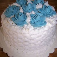 "Small Wedding Cake A 6"" wedding cake done in a simple basketweave with blue roses covering the top."