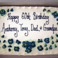 A Grandpa's Birthday Cake Gold cake, buttercream frosting with yellow tipped blue roses and buds.