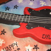 Rock & Roll Buttercream frosting on sheetcake, and I used the Wilton guitar pan and cut it into an electric guitar, covered in fondant