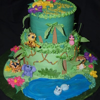 Jungle Themed Cake This is a tiered cake, iced in buttercream. The animals were molded from gumpaste, as were the leaves and bushes around the cake.