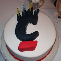 "121536539173870.jpg I cut the ""C"" out of cake and then covered it with black fondant. The cake is also covered in fondant."