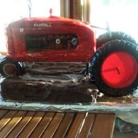 Tractor Farmall 1949 H I made this for a birthday, tractor is fondant and cake, tires are fondant on the outside, inside is plastic, bottom is cake