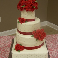 Red Roses Wedding white cake iced with vanilla butter cream icing. Silver dragees on the side. Roses and ribbon are made from fondant. Topper provided by the...