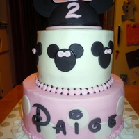 "Minnie Mouse Cake With Ruffles This is a 9""/6"" round two tier cake frosted in buttercream with fondant accents. The Minnie hat is half a styrofoam ball covered..."