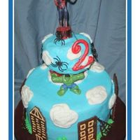 "Super Hero Cake With Spiderman And Hulk 4"" dark chocolate cake over 10' confetti cake with strawberry creme filling and bc icing. Hershey bar houses. Fondant number 2..."