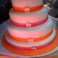 Layered With Ribbons covered with fondant, ribbon around each layer and a royal icing flower
