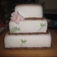 Bamboo Cake Fondant covered with fondant bamboo stalks. Flowers also made from fondant