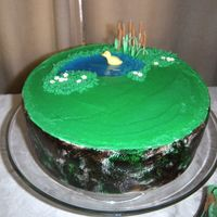 Camoflauge Baby Shower Cake is wrapped with fondant and covered in buttercream. Pond is piping gel and all decorations are gumpaste. The fondant is painted like...