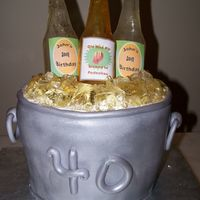 "Beer Bucket 3 sugar bottles in a fondant covered cake ""Bucket"" with sugar ice cubes. this cake was for a 40th birthday."