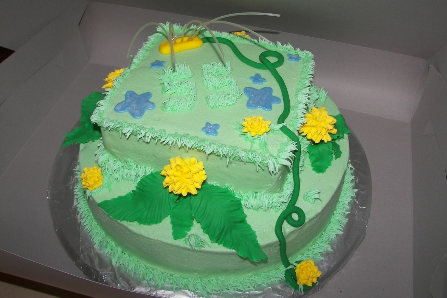 Yard Cake... Buttercream with royal dandelions and fondant leaves... royal grass and fondant puddles painted with luster dust for shine... Sprinkler and...