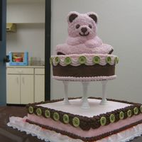 "Pink And Brown Stand Up Bear Pink stand-up bear sits on 10"" round cake. Columns hold bear and round on 14"" square cake. Decorated with chocolate buttercream..."