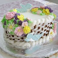 "Basket Cake For Wilton Course 2 Cake is covered with buttercream, and flowers are royal icing. Flavor of the cake is a ""love cake"" (white chocolate cake)"