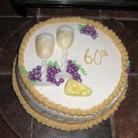 60Th Birthday Beer spice cake covered in BC. I used fondant for the wine glasses, cheese and grapes and luster dust. Thanks to four321 for the design!...