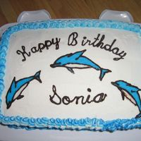 Dolphin Birthday Chocolate and vanilla cake with custard filling and BC. Dolphins made of hardened chocolate outline and RI.