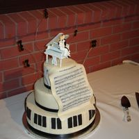 Piano/musical Cake Fondant covered cake with fondant keys, edible image on the sheet music and notes on the top tier.