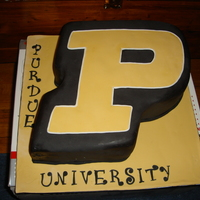 "Purdue U Grooms Cake Irish Car Bomb Cake covered in Fondant as the Purdue ""P"" logo. 3 1/2 sheet cakes filled and carved. Big cake. 4' high."