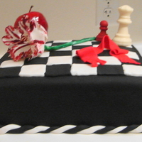 Twilight Cake Red Velvet Cake, covered in fondant w/fondant checkerboard pattern, RKT apple covered in fondant, Gumpaste flower, Chocolate chess pieces,...