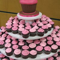 Pink & Brown Cupcakes This is a 3-tiered cupcake stand with 280 chocolate cupcakes for a pink and brown wedding. A large fondant-covered cupcake-shaped cake on...