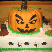 Haloween/pumpkin Cake Pumpkin Spice Jack-O-Lantern covered in Fondant with gumpaste leaves and fondant eyes, nose, mouth. Vanilla two layer cake under it frosted...