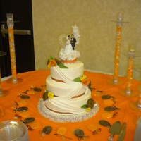 Orange And Brown Round Wedding Cake covered in bc with fondant swag and flowers