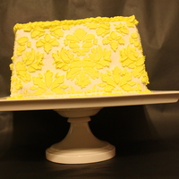 "Yellow Damask Cake 8"" square cake filled with raspberry filling. Butercream covered and damask pattern in yellow buttercream."