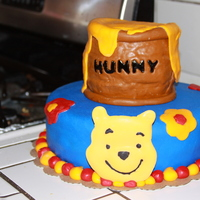Winnie The Pooh Birthday cake covered in fondant. Decorations in fondant and candy metls. The Pooh head was made using a Pooh cake pan and candy melts.